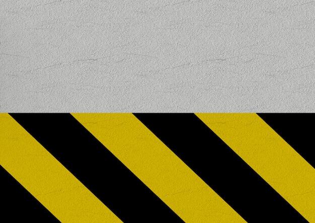 Schwarze und gelbe vorsichtlinie auf zementwandhintergrund.