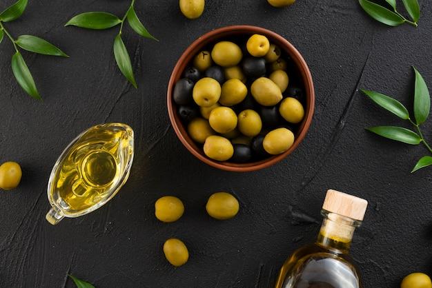 Schwarze und grüne oliven auf schwarzem hintergrund