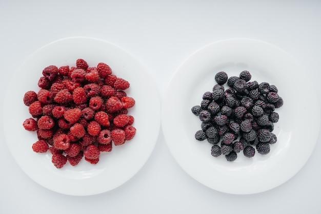Schwarze und rote himbeer-nahaufnahme auf einer weißen oberfläche. gesunde ernährung, natürliche vitamine. frische beeren.