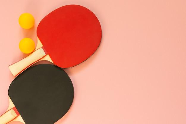 Schwarze und rote tennis-ping-pong-schläger und orangefarbene bälle einzeln auf rosafarbenem hintergrund, sportgeräte für tischtennis