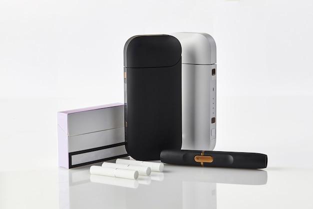 Schwarze und weiße batterien der neuen generation für elektronische zigaretten, eine packung, drei heizstäbe, isoliert auf ...