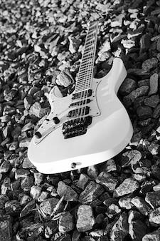 Schwarze und weiße e-gitarre auf den bahngleisen und industriegrauem stein
