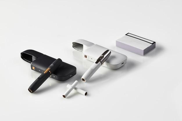 Schwarze und weiße elektronische zigaretten und batterien der neuen generation, eine packung und zwei heizstäbe isola...