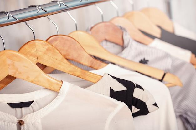 Schwarze und weiße frauenkleider auf hölzernen kleiderbügeln auf einem gestell in einem modegeschäft. schrank geschäftsfrau