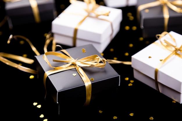 Schwarze und weiße geschenkboxen mit goldenem band auf glänzender oberfläche,