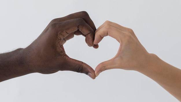Schwarze und weiße hände, die eine herzform bilden