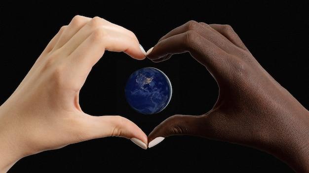 Schwarze und weiße herzförmige hände mit dem planeten erde: amerika im dunkeln. elemente dieses bildes mit freundlicher genehmigung der nasa. erdschutzkonzept
