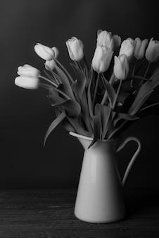 Schwarze und weiße tulpen in einem krug