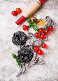 Schwarze ungekochte nudeln mit tomaten und basilikum