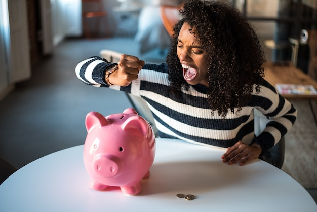Schwarze unglückliche frau verärgert am sparschwein