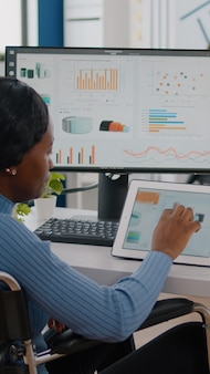 Schwarze unternehmerin mit bewegungsbehinderungen mit tablet und pc