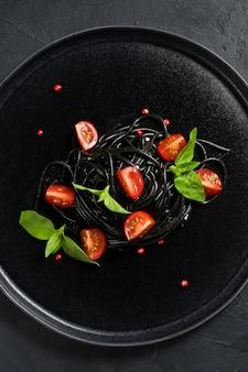 Schwarze vegetarische teigwaren mit basilikum- und kirschtomaten.