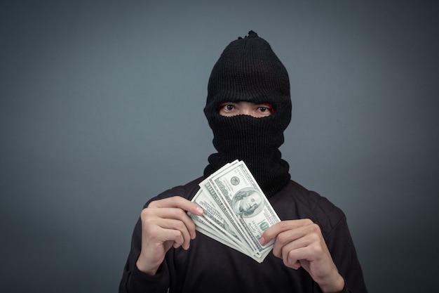 Schwarze verbrecher tragen ein hauptgarn, halten eine dollarkarte auf grau