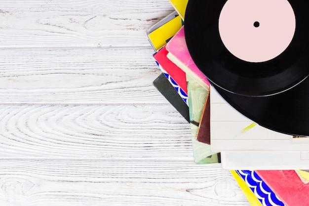 Schwarze vinylaufzeichnungen auf dem holztisch, selektiver fokus mit copyspace. ansicht von oben