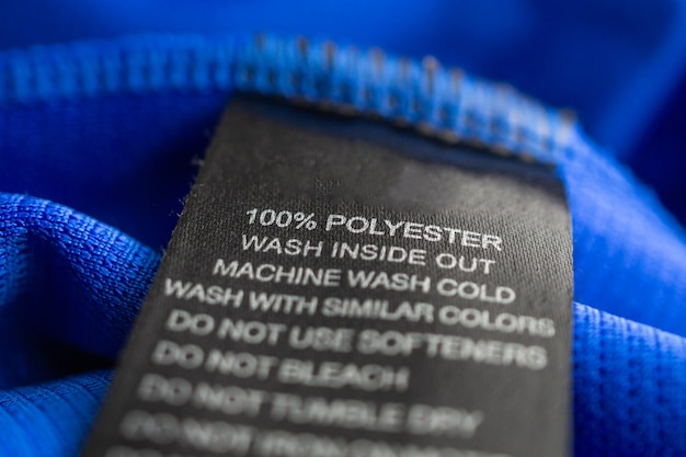 Schwarze wäschepflege waschanleitung kleidungsetikett auf blauem jersey-polyester-sporthemd
