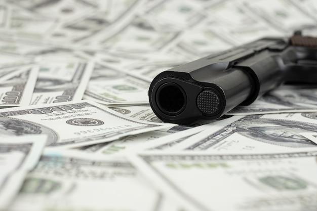 Schwarze waffe auf geldstapel