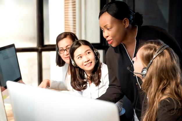 Schwarze weibliche aufsichtskraft, die mit kollegen in call-center arbeitet