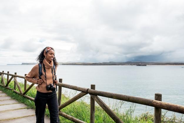 Schwarze weibliche reisende, die das plätschernde meer fotografieren