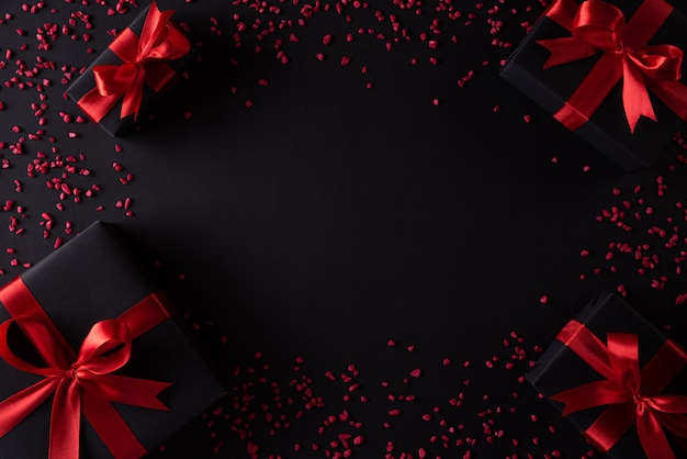 Schwarze weihnachtskästen mit rotem band auf schwarzem hintergrund