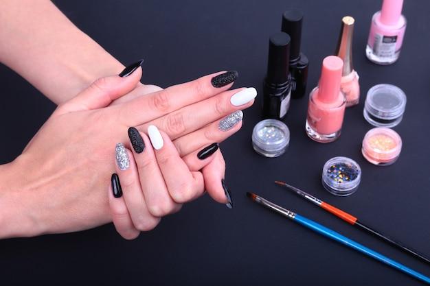 Schwarze, weiße nail art maniküre. flasche nagellack.