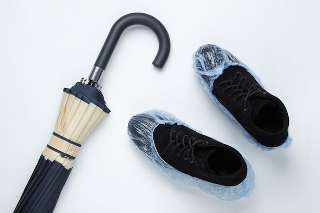 Schwarze wildlederstiefel mit stiefelüberzügen, ein regenschirm auf einem weißen tisch. draufsicht. flach liegen