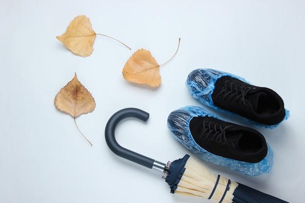 Schwarze wildlederstiefel mit stiefelüberzügen, regenschirm und laub auf einem weißen tisch. draufsicht. flach liegen