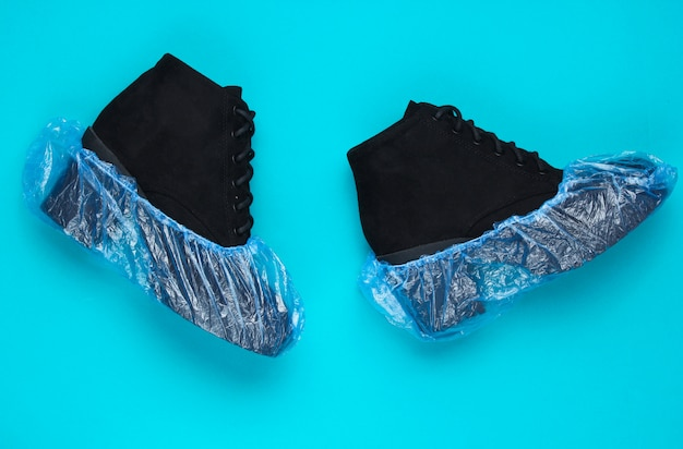Schwarze wildlederstiefel mit überschuhen auf blauem tisch. draufsicht