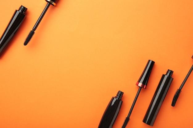 Schwarze wimperntusche und tube auf orangem hintergrund. ansicht von oben