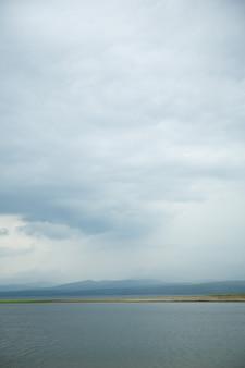 Schwarze wolken mit regen in bergen und über wasser