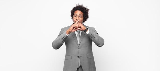 Schwarzer afro-geschäftsmann, der ernst aussieht und unzufrieden ist, wobei beide finger vor ablehnung gekreuzt sind und um stille bitten