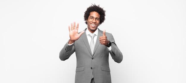 Schwarzer afro-geschäftsmann, der freundlich aussieht und mit der hand nach vorne die nummer sechs oder sechs zeigt und herunterzählt