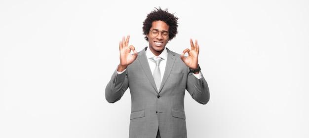 Schwarzer afro-geschäftsmann, der konzentriert und meditierend aussieht, sich zufrieden und entspannt fühlt, denkt oder eine wahl trifft