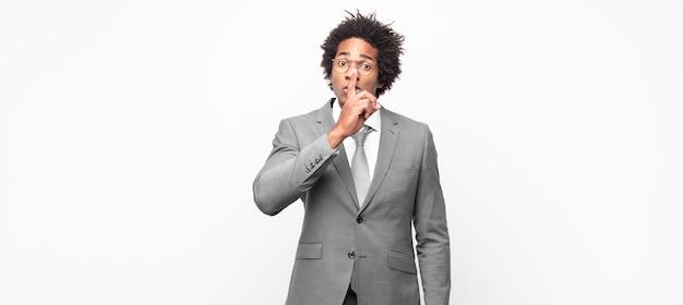Schwarzer afro-geschäftsmann, der nach stille und ruhe fragt, mit dem finger vor dem mund gestikuliert, shh sagt oder ein geheimnis bewahrt