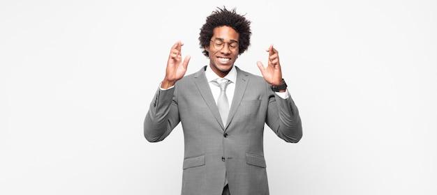 Schwarzer afro-geschäftsmann, der sich nervös und hoffnungsvoll fühlt, die daumen drückt, betet und auf viel glück hofft