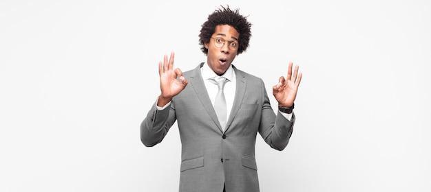 Schwarzer afro-geschäftsmann, der sich schockiert, erstaunt und überrascht fühlt und seine zustimmung zeigt, mit beiden händen ein gutes zeichen zu setzen