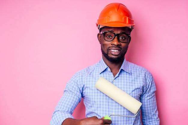Schwarzer afroamerikaner, der farbroller in der hand hält, malt die wand in rosa farbe. glücklicher afrikanischer baumeister, der im haus malt, geschäftsmann trägt einen helmschutzhelm. junger mann malt
