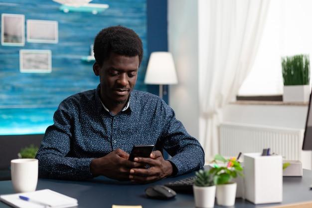 Schwarzer afroamerikaner, der zu hause ein smartphone benutzt