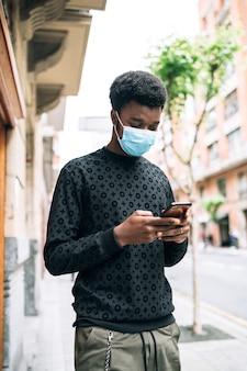 Schwarzer afroamerikanerjunge, der die straße mit einer blauen gesichtsmaske entlang geht, die sein handy betrachtet, das sich vor der covid-19-coronavirus-pandemie schützt
