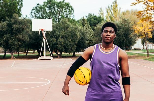 Schwarzer afroamerikanischer junge, der basketball mit einem gelben ball auf einem platz spielt. mit einem lila ärmellosen hemd bekleidet