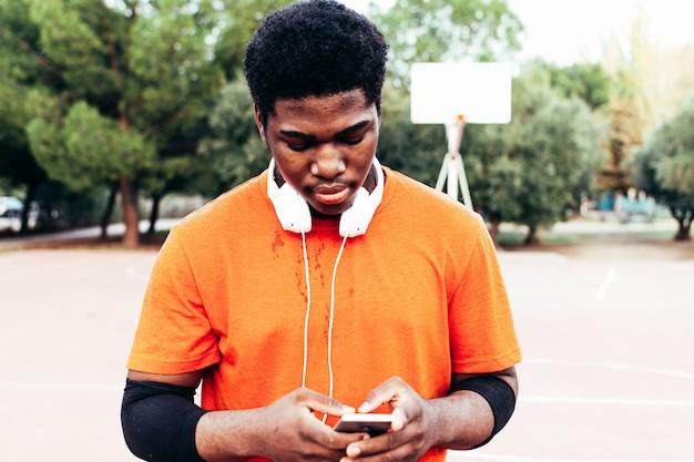 Schwarzer afroamerikanischer junge, der musik mit kopfhörern und seinem handy hört, nachdem er basketball auf einem städtischen platz gespielt hat. mit einem orangefarbenen t-shirt bekleidet.