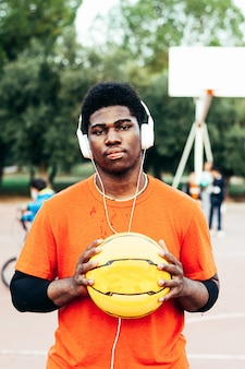Schwarzer afroamerikanischer junge, der musik mit kopfhörern und seinem handy hört, nachdem er basketball auf einem städtischen platz gespielt hat.