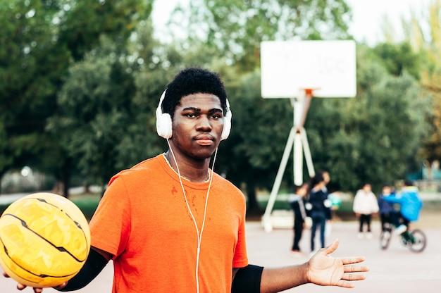 Schwarzer afroamerikanischer junge, der musik mit kopfhörern und seinem handy hört und basketball auf einem städtischen platz spielt. mit einem orangefarbenen t-shirt bekleidet.