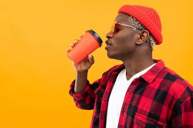 Schwarzer amerikanischer mann im karierten roten hemd trinkt seitlichen kaffee auf gelb mit raum