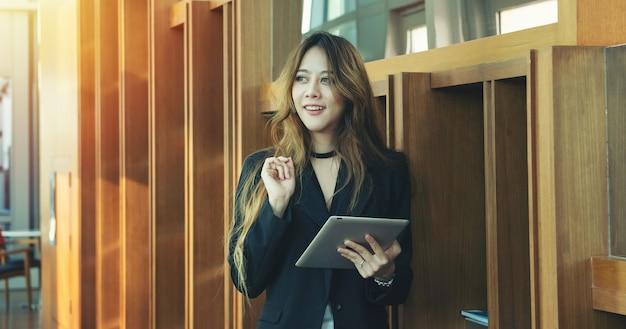 Schwarzer anzug der schönheitsarbeitskleider kleiden braunes langes haar verwenden tablette in ihrem büro. geschäftsmädchen ues wifi drahtloses internet der dinge netzwerkkonzept.