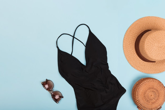 Schwarzer badeanzug mit sonnenbrille und strohhut für den sommer. flatlay, textfreiraum