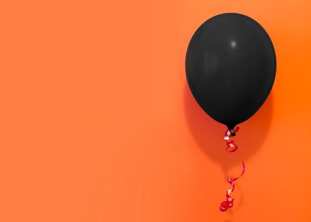 Schwarzer ballon auf orange hintergrund
