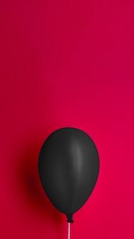 Schwarzer ballon auf rotem hintergrund