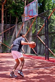 Schwarzer basketball-spieler, der auf dem gebiet spielt