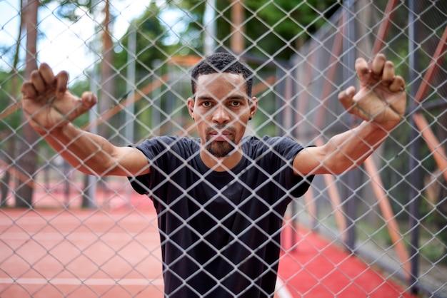 Schwarzer basketball-spieler, der den kettengliedzaun mit den händen hält