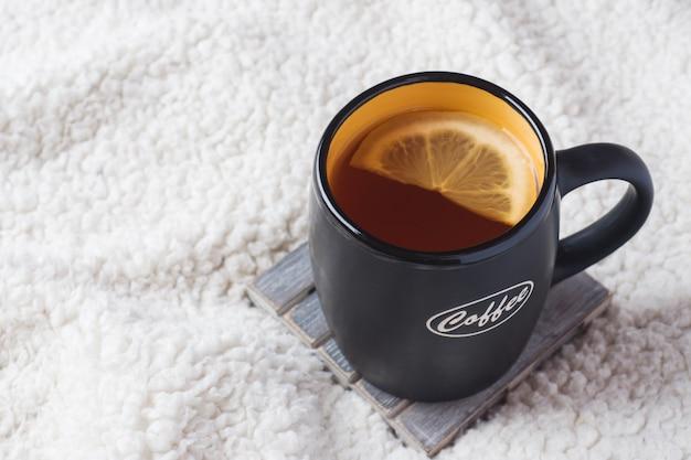 Schwarzer becher mit tee und zitrone auf einer warmen weichen decke
